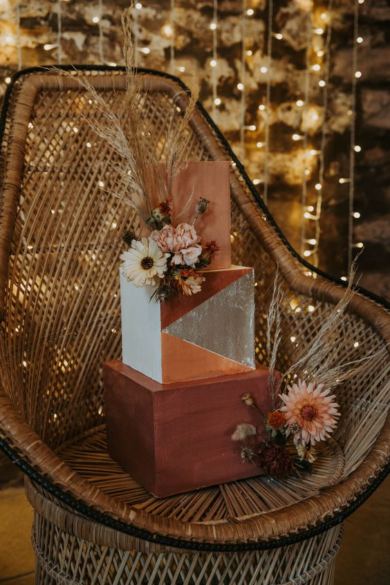a statement square wedding cake with a terraccotta, rust and color block tier, dried blooms and pampas grass is amazing