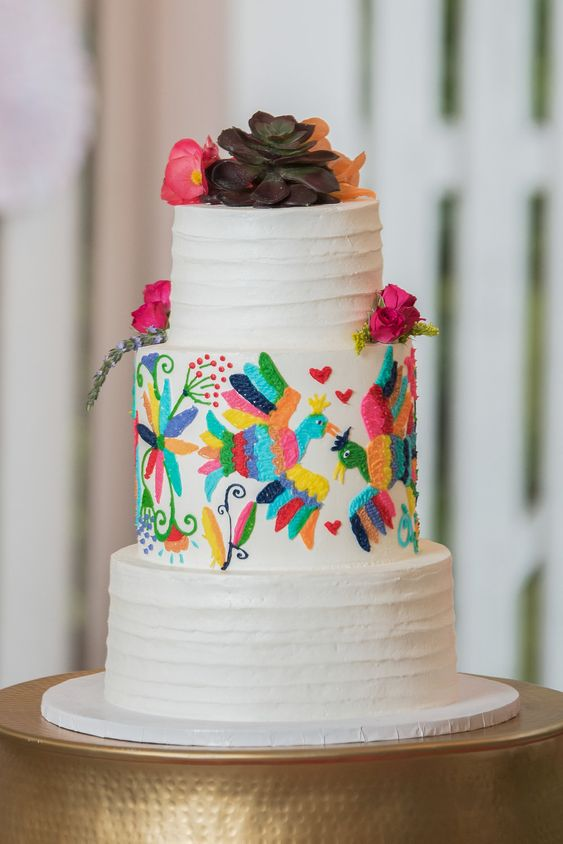 a bold textural wedding cake in white, with a colorful bird pattern, with blooms and a succulent on top is a fun idea for any colorful wedding