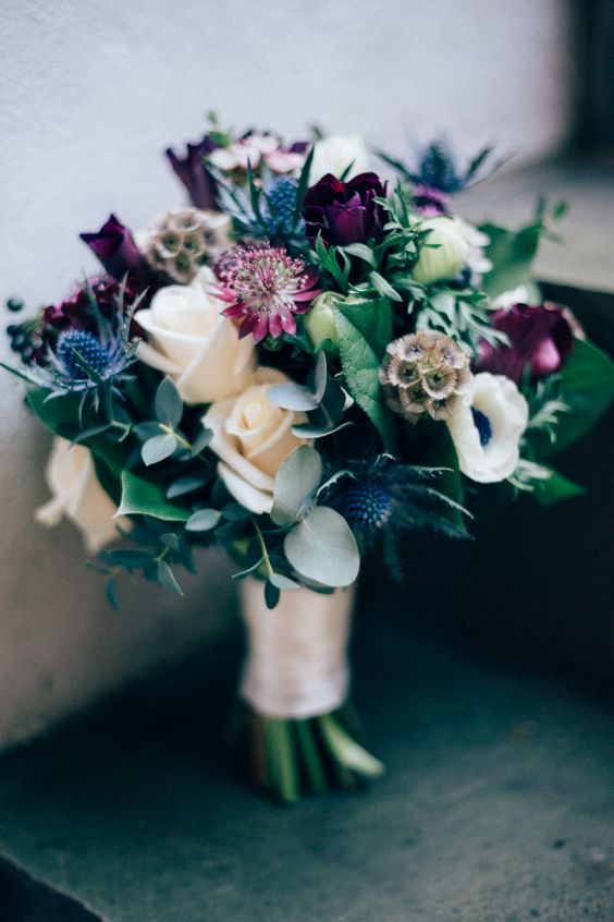 a lovely winter wedding bouquet with white roses, purple ones, anemones, thistles and greenery plus seed pods