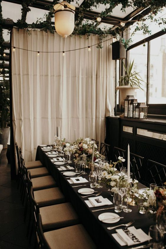 a modern glam wedding tablescape with a black tablecloth, white candles and blooms and white linens is amazing