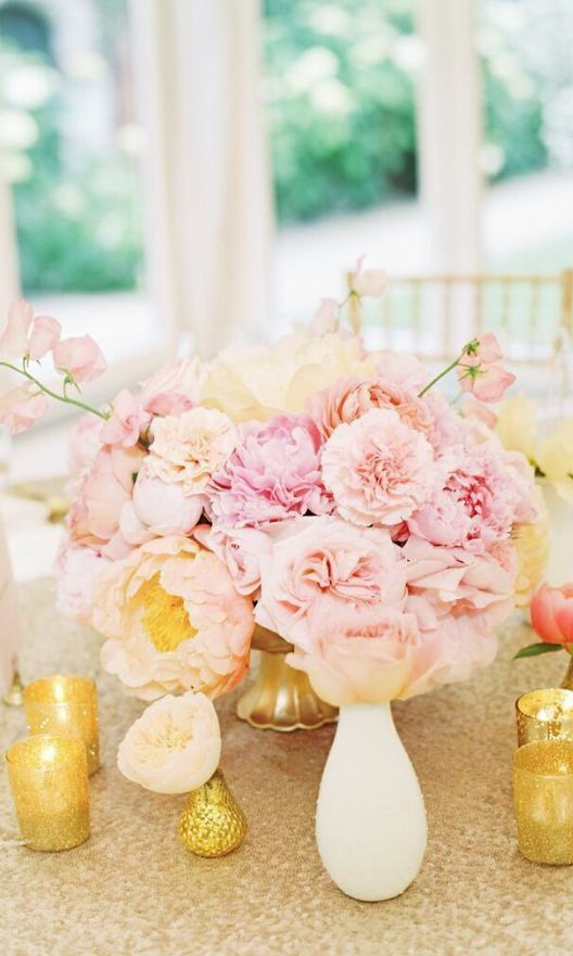 a simple and pretty wedding centerpiece of blush peonies in a gold bowl surrounded with gilded candleholders