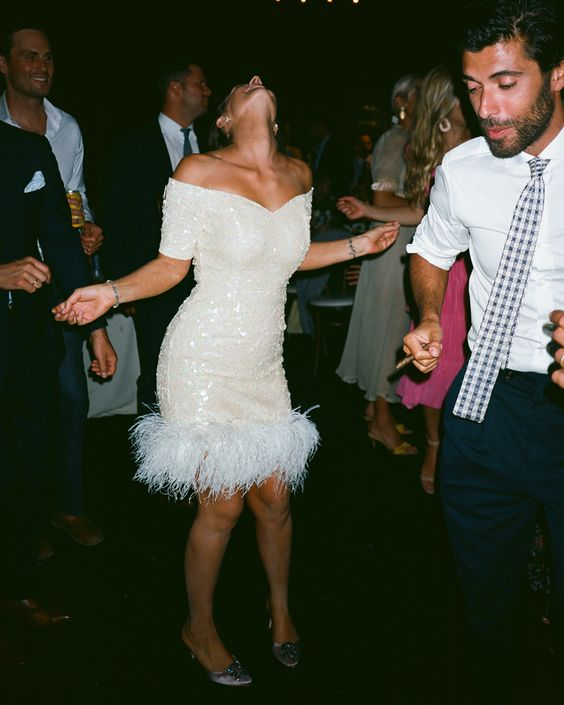 a white sequin off the shoulder over the knee dress with feathers is ideal for a wedding reception for a fun glam wedding