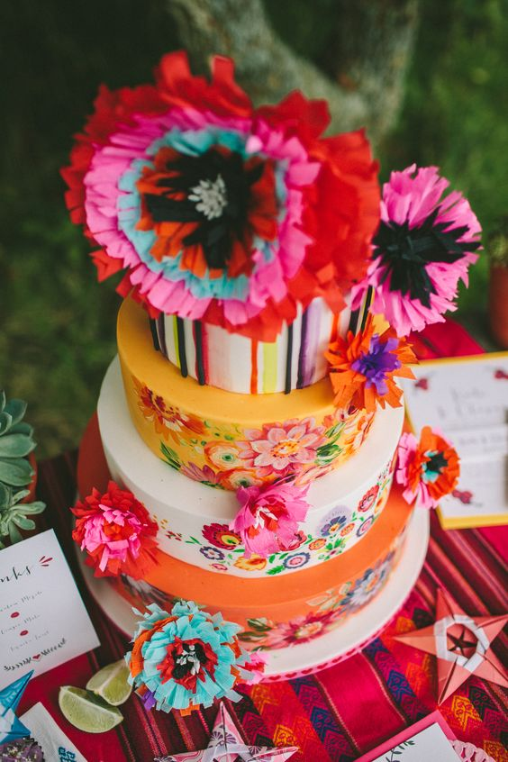 a bright and fun Mexican wedding cake with floral patterns and stripes, bold paper blooms for a Mexican wedding