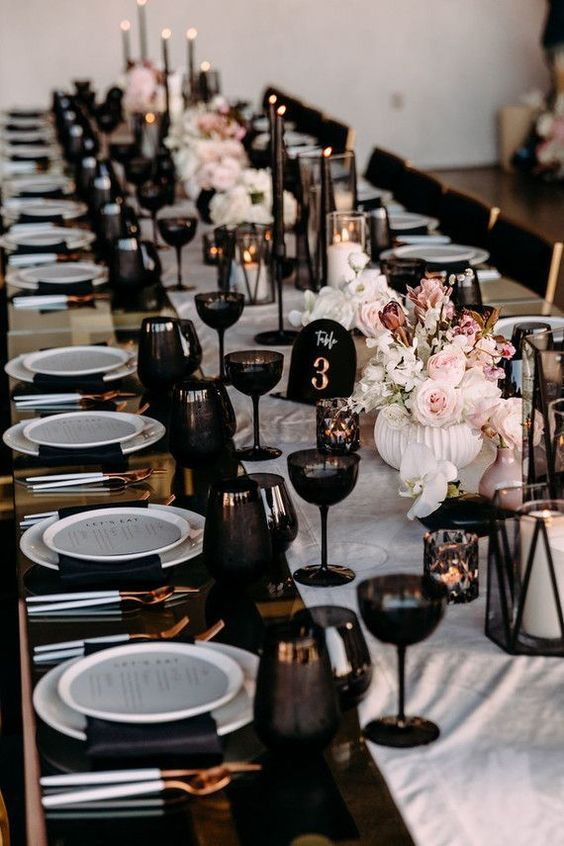 20 a modern glam wedding tablescape with a neutral runner, black napkins and glasses, black candleholders and blush and white floral arrangements