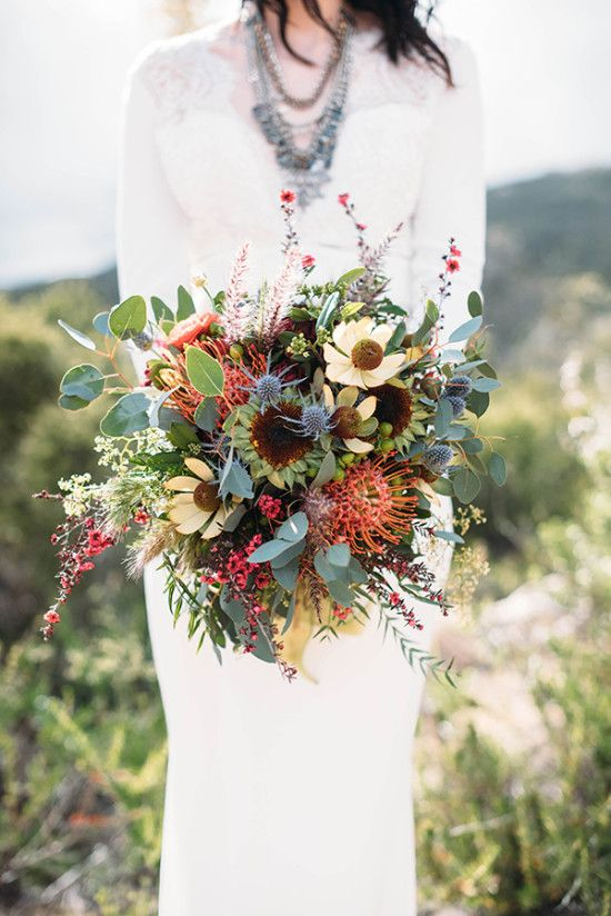 a pretty boho fall wedding bouquet with yellow and brown blooms, pincushion proteas, eucalyptus and thistles is wow
