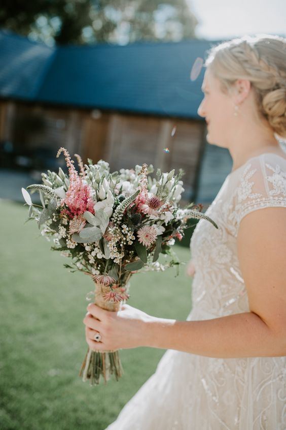 a rustic wedding bouquet with pink and white blooms and astilbe, foliage and wildflowers for a relaxed summer wedding
