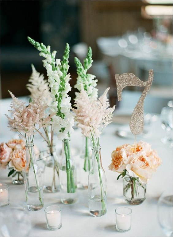 a breezy cluster wedding centerpiece of clear bottles with white blooms and blush astilbe, peachy peony roses and a glitter table number