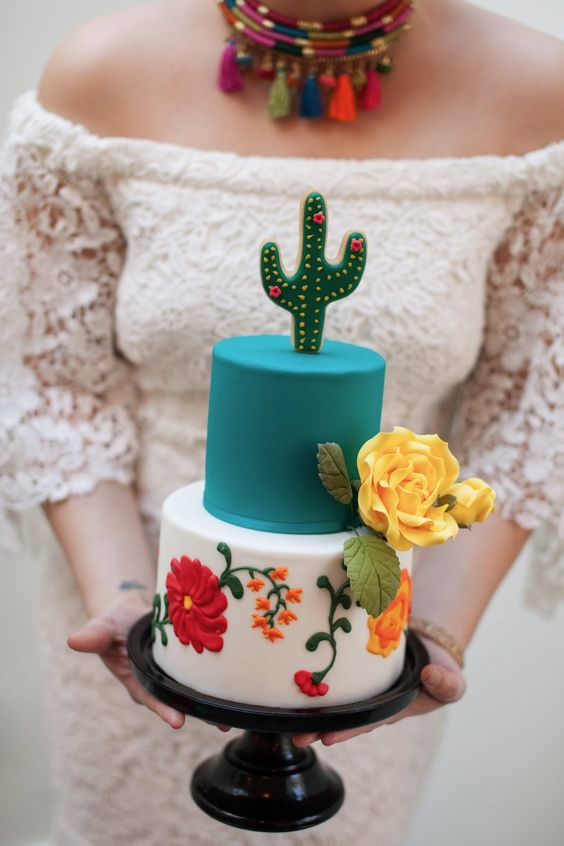 a bright Mexican wedding cake with a white and a turquoise tier, floral patterns and a cactus topper is a fun idea