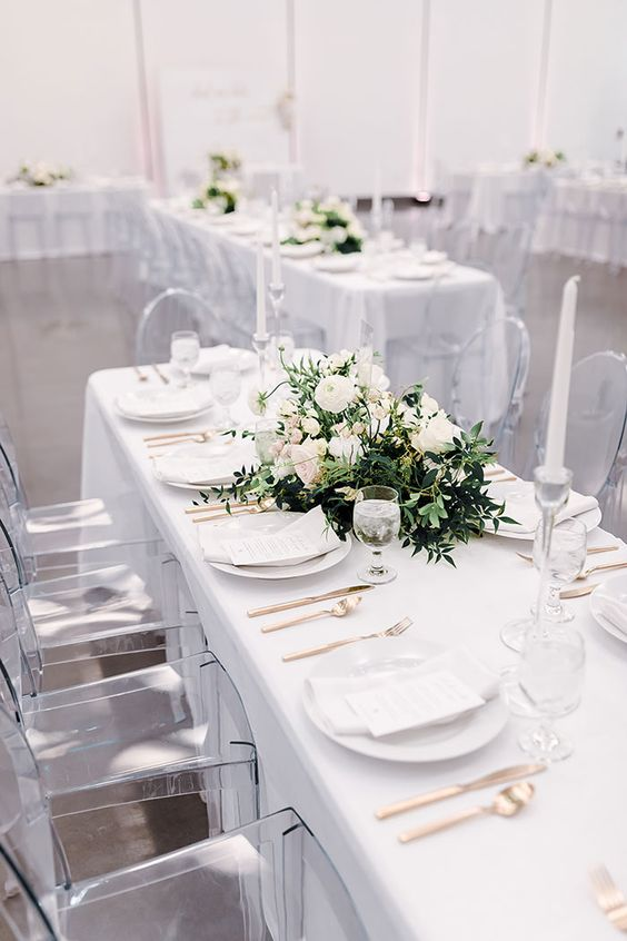 a modern glam wedding tablescape with white linens and plates, with brass cutlery and a lush greenery and neutral bloom wedding centerpiece