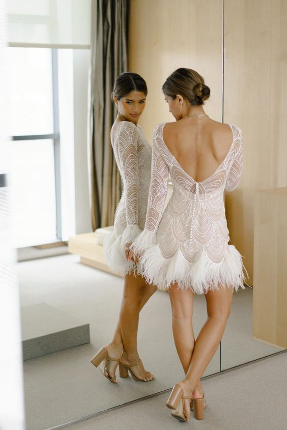 21 a playful beaded lace a-line mini dress with long sleeves, an open back and feathers on the edge for a glam and chic reception look