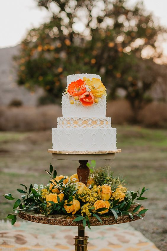 21 a pretty boho wedding cake with a yellow tier and lace patterns and bold fresh blooms feels very 70s and boho-like