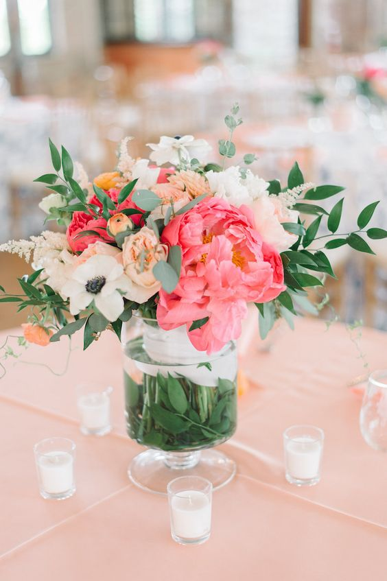 a pretty wedding centerpiece with coral peonies, white ranunculus, blush blooms and foliage for a spring or summer wedding