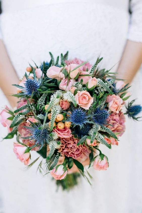 a romantic wedding bouquet with light pink roses, berries, white touches and thistles is amazing and cool