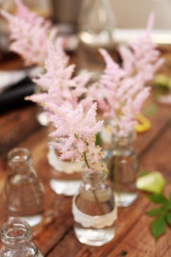 a cluster wedding centerpiece of clear bottles and pink astilbes is a pretty and lovely idea to realize yourself