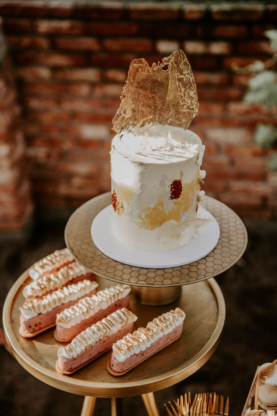 a pretty boho chic 70s wedding cake with yellow and burgundy brushstrokes and clear sugar shards on top is amazing