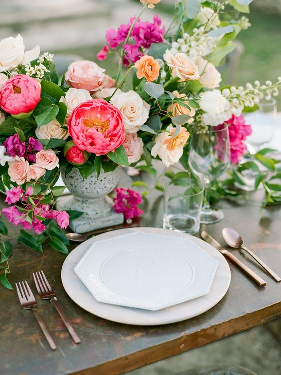 a refined summer wedding centerpiece with coral peonies, white and blush roses, hot pink blooms and greenery is jaw-dropping