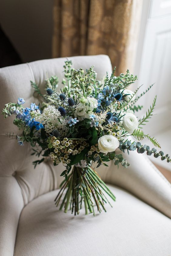 a stylish wedding bouquet with white blooms, blue ones, thistles and some greenery looks ethereal and chic
