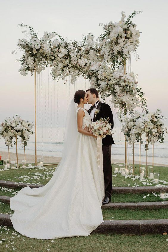a modern luxurious wedding altar with lush white blooms and greenery plus candles on the ground and a sea view