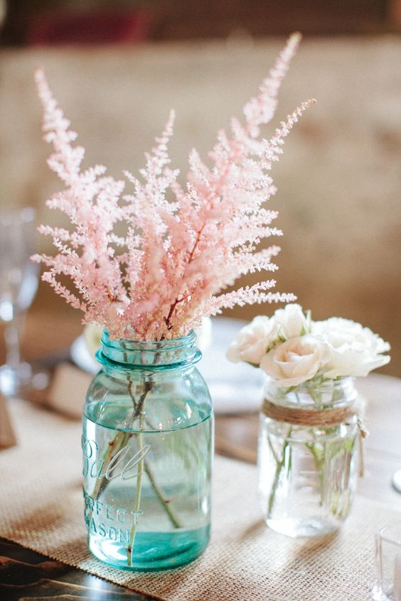 a cool wedding centerpiece of a blue jar with pink astilbe and a clear jar with small white roses for a rustic wedding