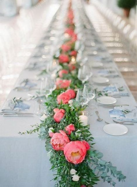 a cool wedding table runner of greenery, coral peonies and white mini blooms is a lovely touch of color toadd to your tablescape