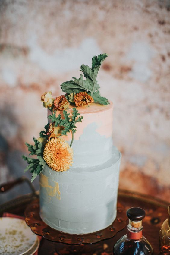 a pastel 70s inspired wedding cake in pastel pink and blue, with rust colored flowers and leaves is a non typical solution for a 70s wedding