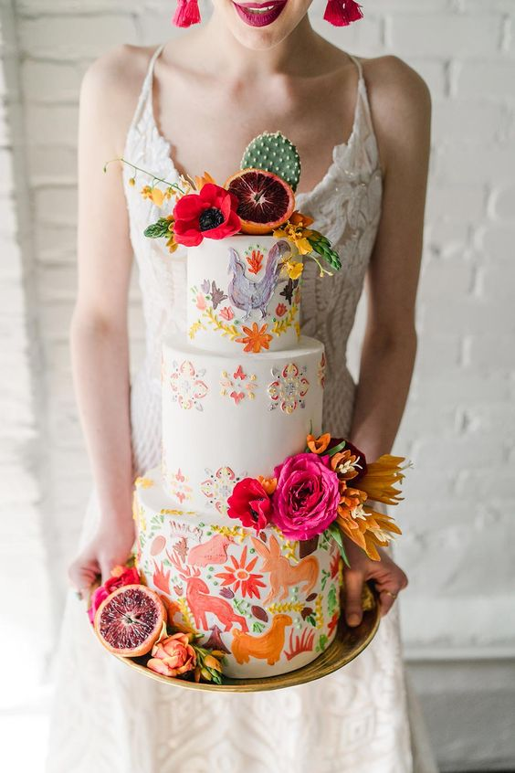 a colorful Mexican wedding cake with hand painted animals and blooms and bright blooms, citrus and cacti