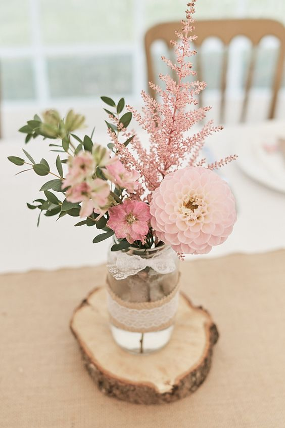 a cozy farmhouse wedding centerpiece of a jar with greenery, pink blooms and pink astilbe put on a wood slice is wow