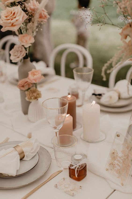 a modern natural glam wedding tablescape with blush floral arrangements, blush and mauve candles, grey plates and brass cutlery