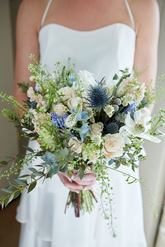 an ethereal wedding bouquet with white and blush blooms, blue ones, thistles and lots of greenery for a chic look