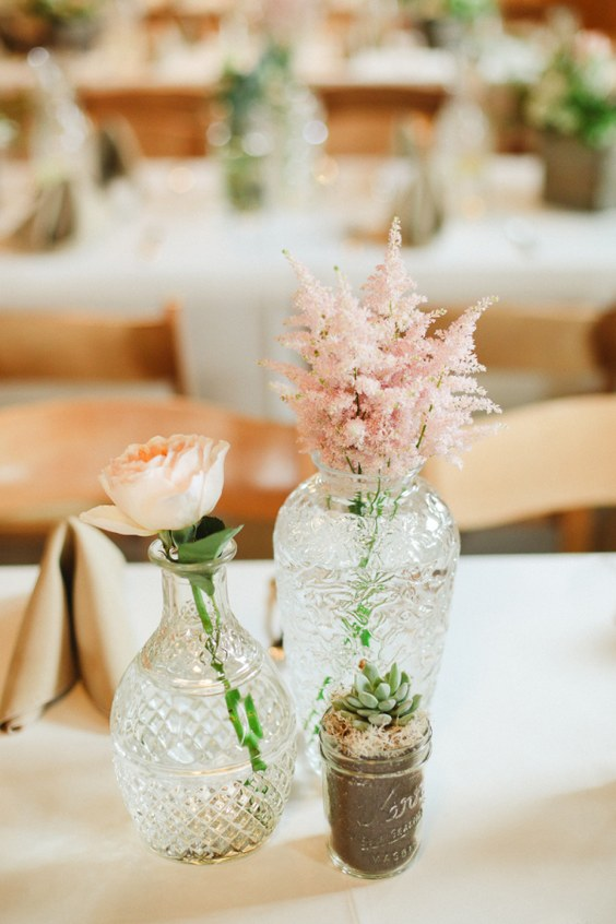 a creative wedding centerpiece of vintage vases with a single blush peony rose and astilbe and a potted succulent for a refined wedding