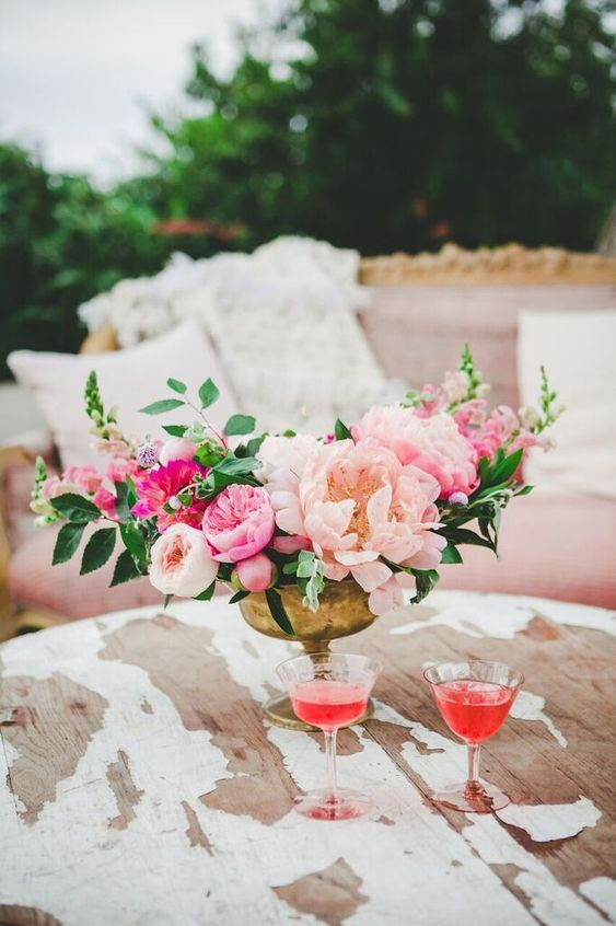 a gorgeous wedding centerpiece of blush peonies, pink peony roses, greenery and a gold bowl is pure chic