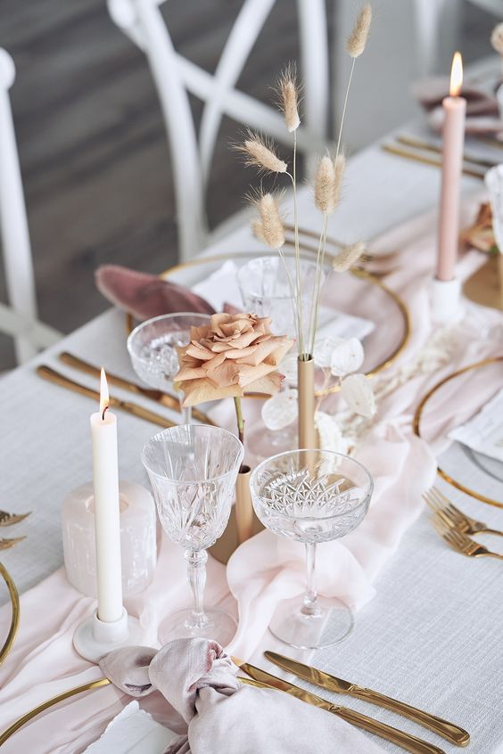 a modern refined wedding tablescape in pastels, with a blush table runner, a coffee rose, a bunny tail arrangement, neutral candles and mauve napkins