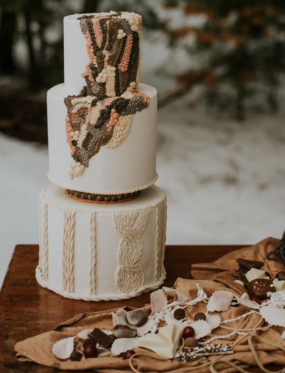 26 a whimsical boho 70s wedding cake with macrame and yarn-like detailing in pink and dark green is a gorgeous idea for a boho wedding