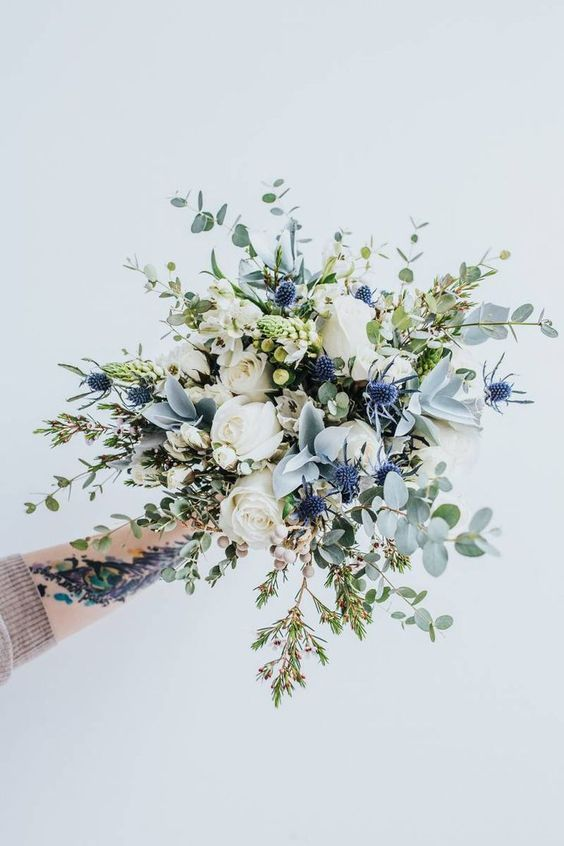 an ethereal wedding bouquet with white roses, thistles, berries and pale greenery is a fantastic idea for a spring or summer bride