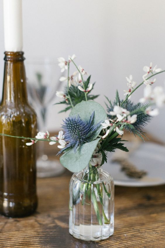 a beautiful wedding centerpiece of a clear vase, white blooms, thistles and leaves is a delicate and subtle idea for your wedding
