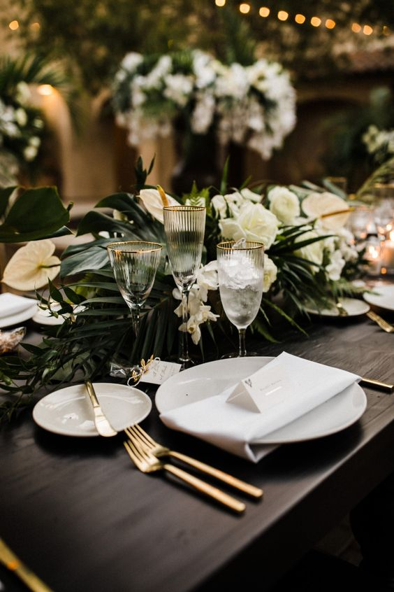27 a modern tropical chic wedding tablescape with a centerpiece of tropical foliage and white blooms, white plates and gold cutlery and candles