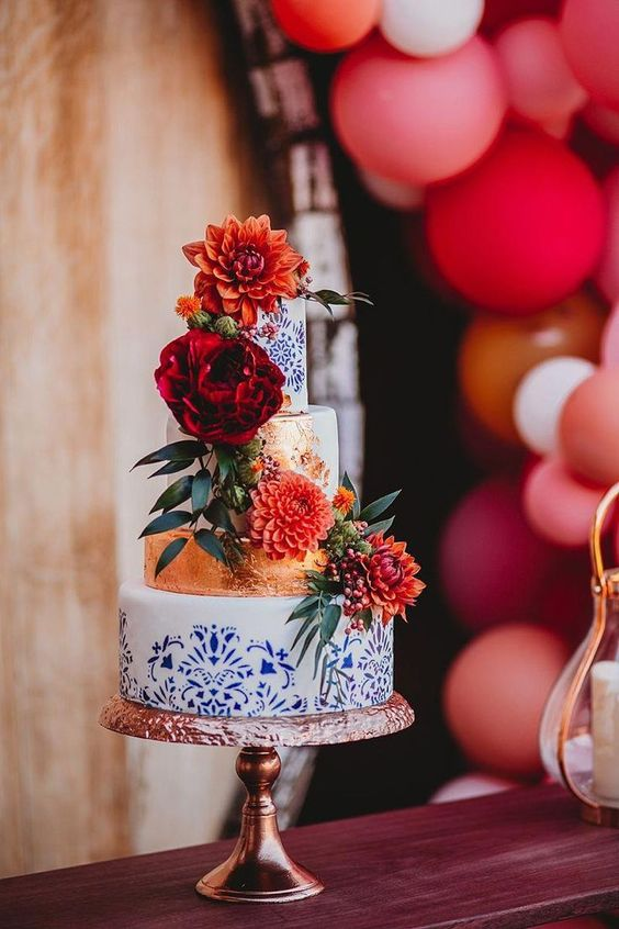 a refined Mexican wedding cake with copper and blue and white printed tiers and bold blooms is amazing