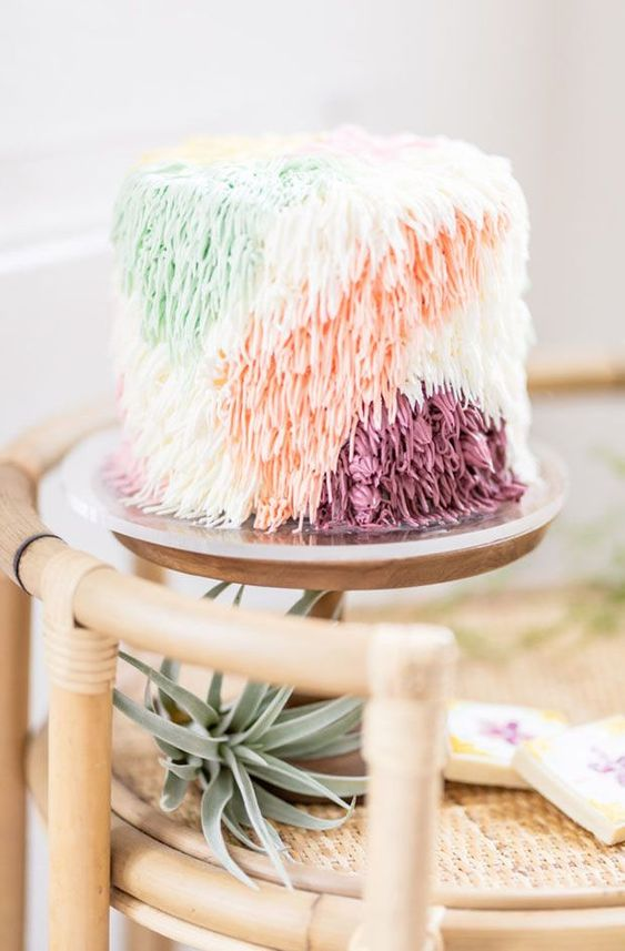 a whimsical wedding cake with color block yarn like decor for a 70s wedding is a lovely idea with a strong boho feel