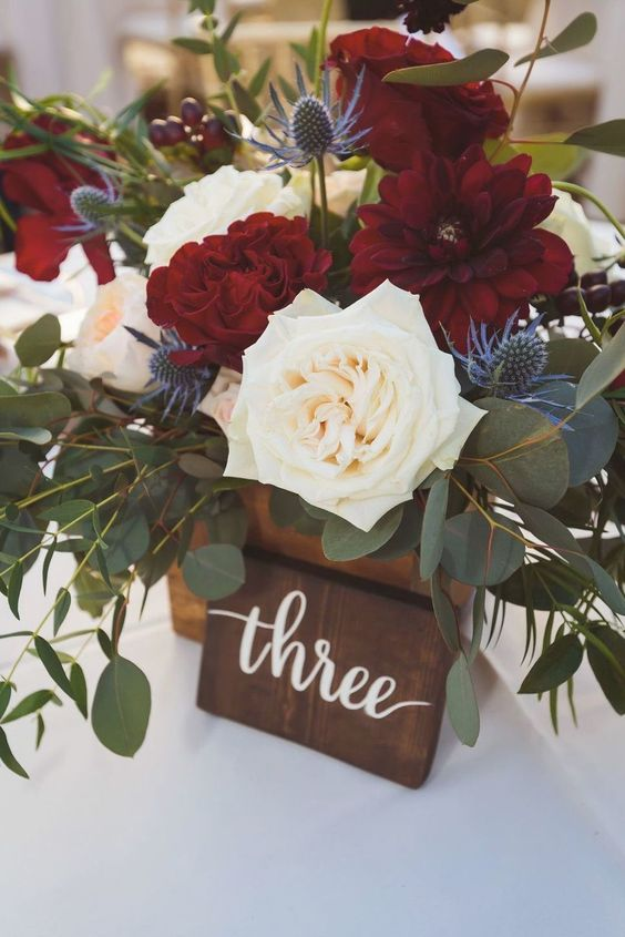 a bold and lovely wedding centerpiece wiht burgundy and neutral blooms, lots of greenery and thistles is adorable and chic