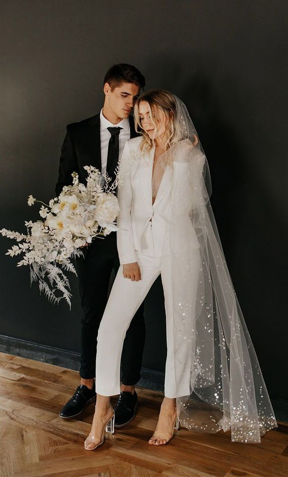 28 a chic white pantsuit with cropped pants, sheer heels and a long veil with sequins for a comfy reception look