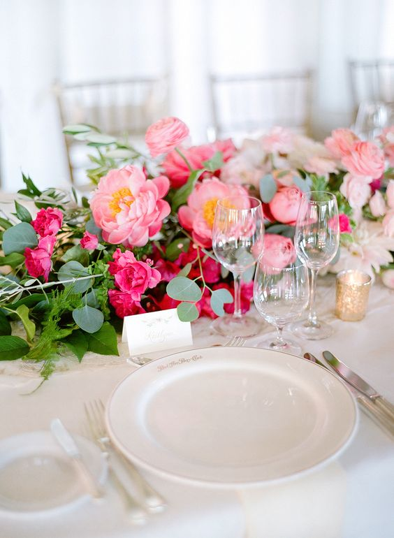 a lush table runner of greenery, hot pink roses and pink peonies is a very beautiful and cool idea to rock