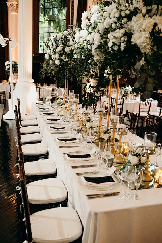 28 a neutral and refined wedding tablescape with neutral linens, black menus, a mirror table runner, lush white florals and candles