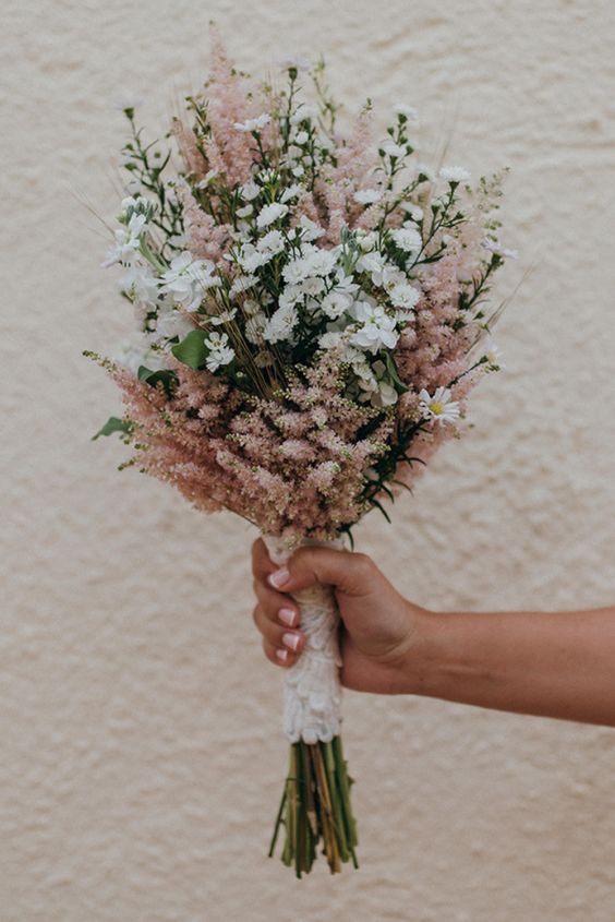 a pretty and simple wedding bouquet with pink astilbe and white wildflowers plus a lace wrap is ideal for a spring or summer boho wedding