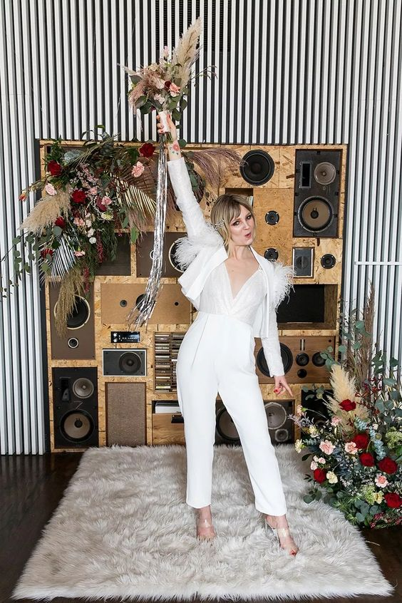 29 a fitting white jumpsuit with a shiny bodice, a bolero with feathers and sheer shoes for a 70s inspried look