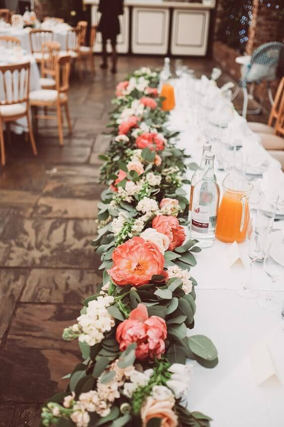 a lush wedding table runner of eucalyptus, blush blooms, coral peonies is a lovely idea for a spring or summer wedding