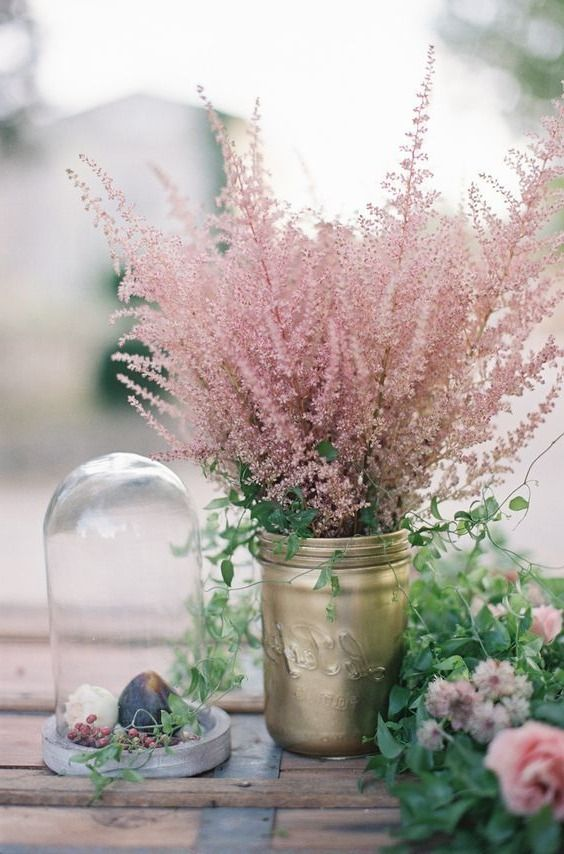 a pretty wedding centerpiece of a gold jar and pink astilbe, a little cloche with figs and greenery on the table for a relaxed wedding
