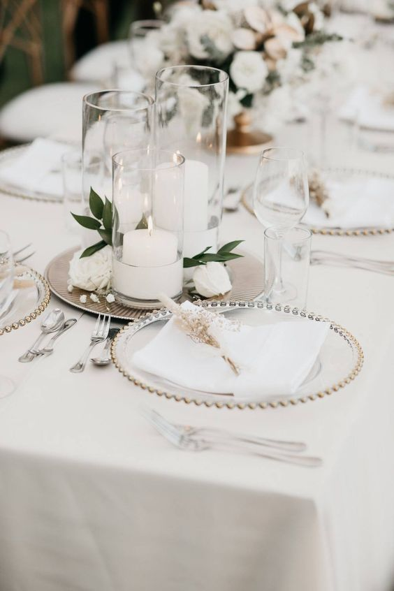 29 a refined wedding tablescape with metallic trays with candles and blooms, sheer chargers and neutral linens with dried blooms