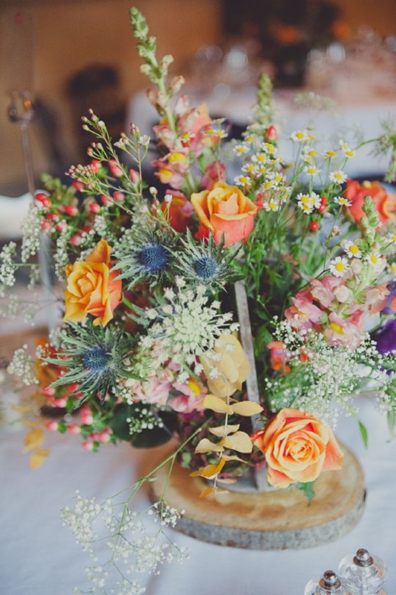a colorful wedding centerpiece with yellow roses, pink blooms, greenery, some wildflowers and thistles for a boho summer wedding