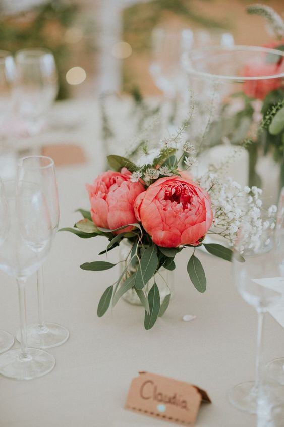 a pretty wedding centerpiece of two coral peonies, baby's breath and foliage is a simple and cute arrangement to make yourself