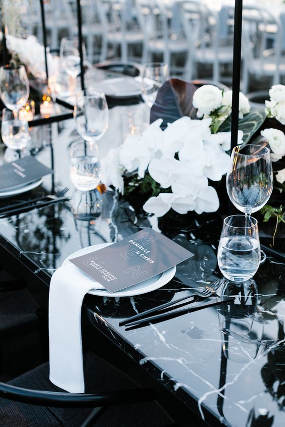 a striking wedding tablescape with an uncovered black marble table, white orchids, black candles and black menus is wow